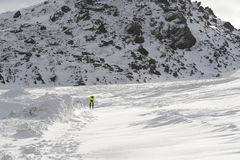 Young healthy sport man running in snow mountains in trail runner hard  workout in winter Stock Photography