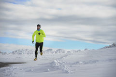 Young healthy sport man running in snow mountains in trail runner hard  workout in winter Stock Photo