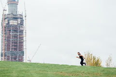 Young healthy sport man running on top of a green hill. Against the backdrop  an unfinished building. hard workout. Young healthy sport man running on top of a Stock Photos