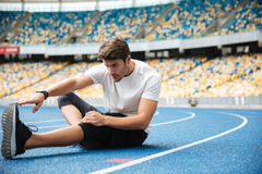 Young healthy sportsman stretching legs. While sitting on a racetrack at the stadium Royalty Free Stock Image