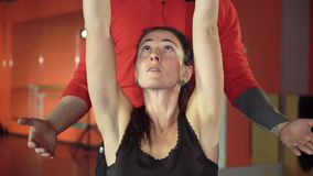 Young healthy sporty active shape girl with a handsome helpful personal trainer next to her in the gym.