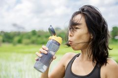 Young healthy sporty Asian Chinese woman drinking water bottle after fitness training and running workout outdoors on green field stock images