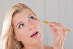 Young healthy woman  applying eye make-up Royalty Free Stock Photos