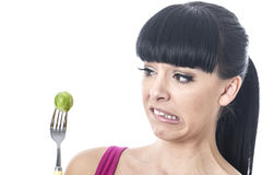 Young Healthy Woman with Disgusted Expression with Distaste to a Brussels Sprout on a Fork Royalty Free Stock Photos
