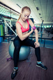 Young healthy woman do physical exercises with dumbbells on fit-ball in gym royalty free stock image