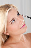 Young healthy woman doing eye make-up with a brush Stock Image