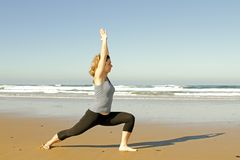 Young healthy woman doing yoga exercises. At the beach Stock Images