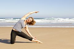 Young healthy woman doing yoga exercises. At the beach Stock Photos