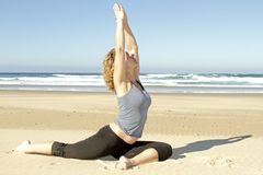 Young healthy woman doing yoga exercises. At the beach Royalty Free Stock Images