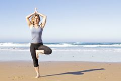 Young healthy woman doing yoga exercises. At the beach Royalty Free Stock Photos