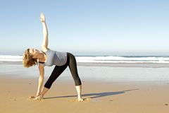 Young healthy woman doing yoga exercises. At the beach Stock Image