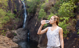 Young healthy woman drinks water from bottle.Outdoor Stock Photos