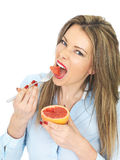 Young Healthy Woman Eating a Pink Grapefruit Stock Images