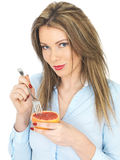 Young Healthy Woman Eating a Pink Grapefruit Stock Photo