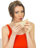 Young Healthy Woman Eating a Salmon and Cucumber Brown Bread Sandwich Royalty Free Stock Image