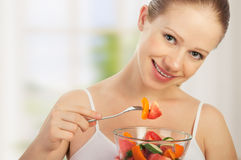 Young healthy woman eats vegetable salad Stock Image
