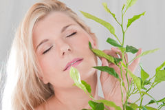 Young healthy woman with green plant Stock Photos
