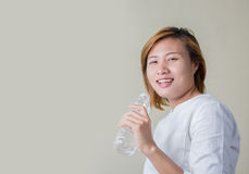 Young healthy woman holding bottle of water and smiles at camera Royalty Free Stock Image