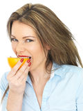 Young Healthy Woman Holding Eating Half an Orange Stock Photo