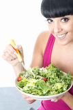 Young Healthy Woman Holding a Large Bowl of Fresh Green Salad Leaves with Tomato Royalty Free Stock Photography