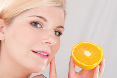 Young healthy woman holding an orange Stock Images