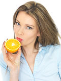 Young Healthy Woman Holding an Orange to Her Lips Royalty Free Stock Photo