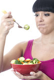 Young Healthy Woman Holding a Red Bowl of Fresh Raw Vegetables with an Expression of Disgust. Healthy young woman, with dark hair, with hispanic or european Stock Images