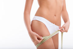 Young healthy woman is measuring her figure Stock Photography