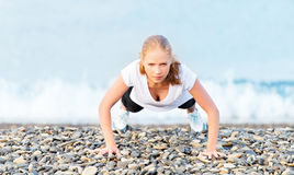 Young healthy woman playing sports push-ups outdoors on the beac Royalty Free Stock Images