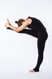 Young healthy woman practicing Balancing stick posture yoga on white background. royalty free stock photography