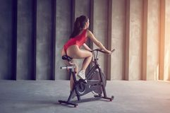 Young healthy woman in red sportswear rides on the exercise bike. Sport and healthy lifestyle concept stock photography