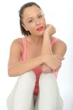 Young Healthy Woman Relaxed and Contented. A DSLR royalty free image, of attractive young woman relaxed and contented sitting on the floor, wearing a pink vest Stock Photos