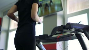 Young healthy woman running on treadmill. 4k stock video footage