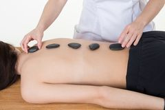 Young and healthy woman in spa salon is having hot stone massage health concept. Beautiful young and healthy woman in spa salon is having hot stone massage royalty free stock photo