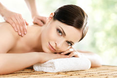 Young and beautiful girl relaxing in spa salon. Massage therapy over seasonal summer or spring background. Healing medicine and h. Ealth care concept stock photography