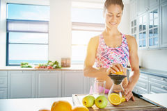 Young healthy woman squeezing juice from orange royalty free stock photography