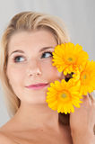Young healthy woman with three yellow flowers Royalty Free Stock Image