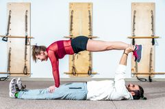 Young healthy yoga fitness acrobatic couple having fun in the gym performing and practicing funny acrobat poses real people traini. Young healthy yoga fitness stock images