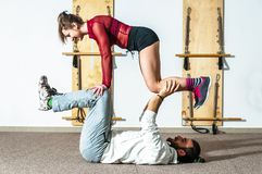 Young healthy yoga fitness acrobatic couple having fun in the gym performing and practicing funny acrobat poses real people traini. Young healthy yoga fitness royalty free stock photos