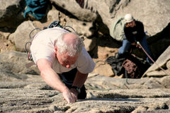 Young at heart. An older rock climber shows the young ones how it is done stock images
