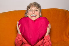 Young at heart. Pensioner smiling while holding a red heart in her hands Royalty Free Stock Images