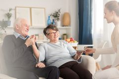 Young at heart senior couple. Young at heart emotional senior couple holding hands while sitting on settee and being served by a caregiver a cup of tea in a Royalty Free Stock Photography