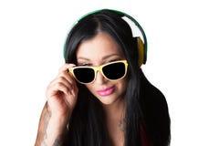 Young heavily tattooed woman Listening headphones. Young heavily tattooed woman Listening to colorful DJ Style Headphones Stock Photo