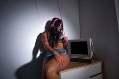 Young heavily tattooed woman sitting on a table watching a tv Royalty Free Stock Images