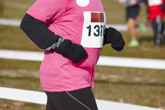 Young heavy female athletic runner on a race. Outdoor circuit Stock Image