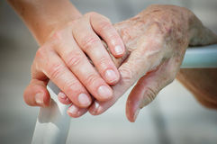 Young help Old. Young and old hand on a backrest Royalty Free Stock Photography