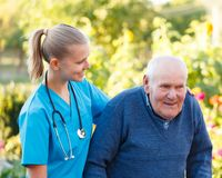 Young helpful doctor. Kind helpful doctor giving support to her elderly patient Stock Image