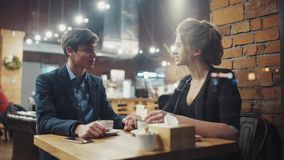 Young heterosexual couple dating, talking and drinking coffee in a cozy modern café. stock footage