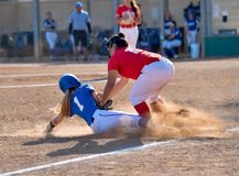 Young High School girl playing in a softball game royalty free stock photography