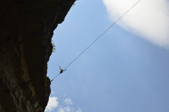 Young highliner walking high on a tightrope in the sky Stock Photography